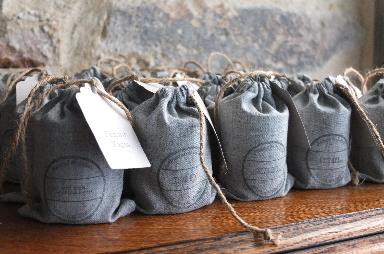Pochons en flanelle grise pour un mariage d'hiver contenant une bougie artisanale les cadeaux pour les invités