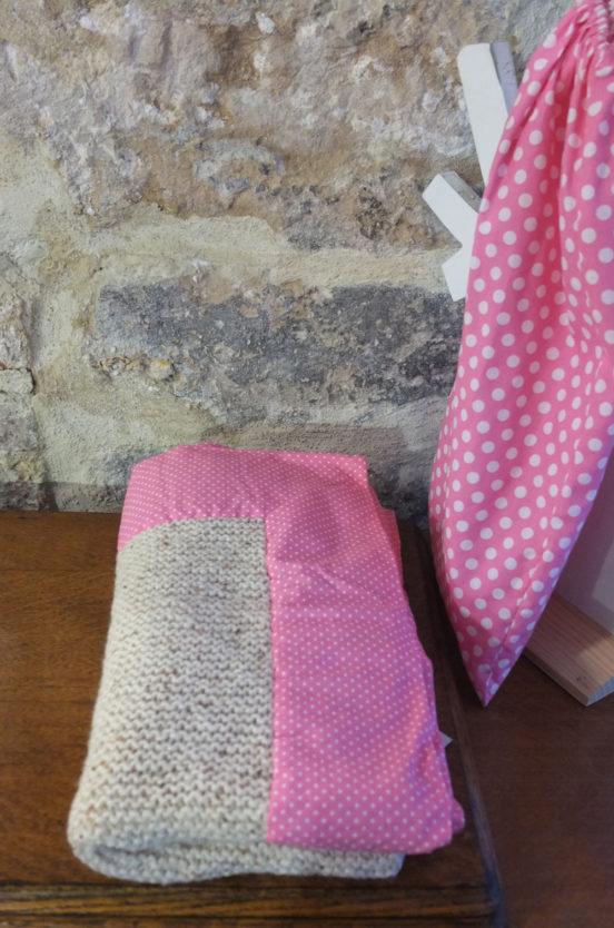 Couverture d'enfant tricotée à la main en laine beige et au contour en tissu rose à petits pois blancs