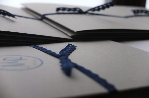 Un faire-part avec un beau papier gris Fédrigoni, impression marine et fermeture avec une dentelle en coton marine